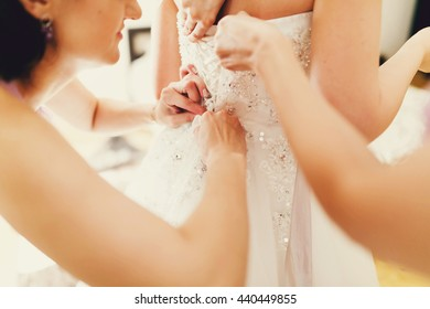 Girls help bride to button up a corset