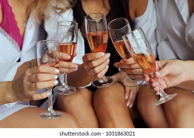 Girls  hold in hands glasses with champagne, friends celebrating and toasting