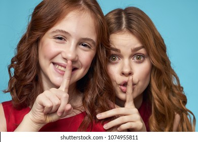 girls hold their fingers at the lips, silence, portrait