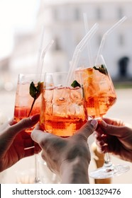 Girls holding aperol spritz cocktails