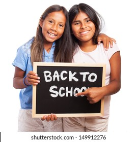 girls holding a chalkboard back to school