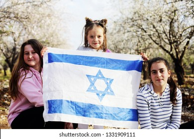 Girls are holding an Israeli flag outdoors
