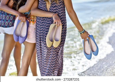 girls hugging each other walking by the sea fashionable