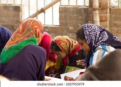 Girls in Indian village school study in a cirlcle, wearing head scarves