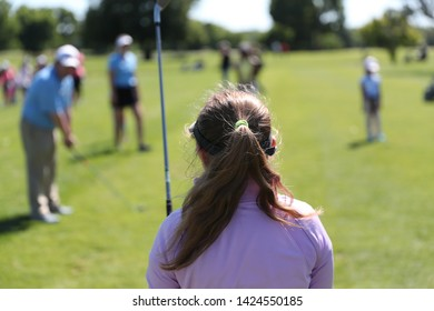 girls are instructed on how to hold and swing a golf club