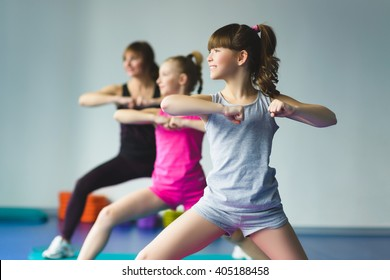Girls and Instructor or mother doing gymnastic exercises  in fitness class