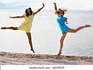 Girls jump on a beach