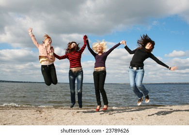 Girls jumping up at the beach