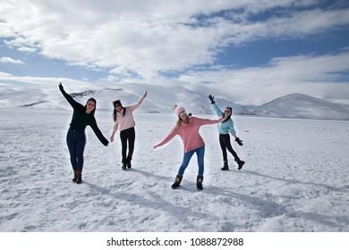 Girls jumping and havin fun on the frozen Cildir Lake (Cildir Golu), Ardahan nearby Kars in Turkey