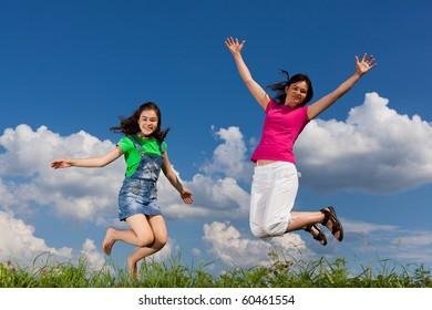 Girls jumping, running outdoor against blue sky