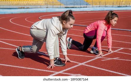 girls kids standing on start before running outside on stadium arena, start.