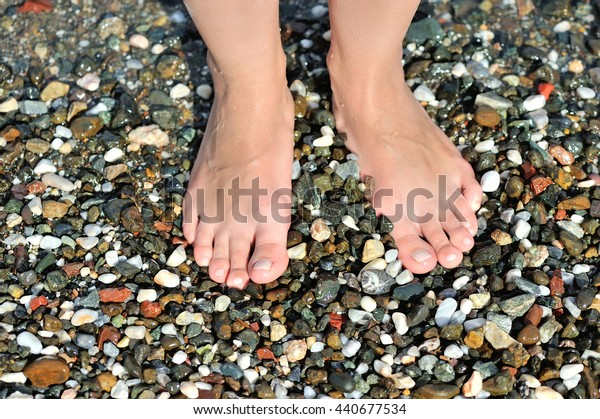Girl's leg on colorful pebbles on the beach by the sea