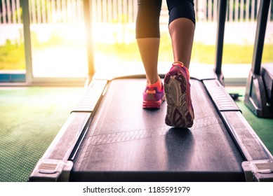 The girl's legs are jogging on the track in the gym.