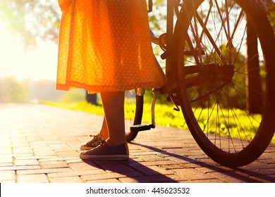 Girls legs and long vintage orange skirt. Close up photo of girl stand with her bicycle in the city park at the sunset.