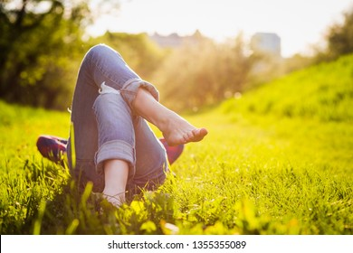 girls legs lying on the grass at sunset time. Spring vacation relax concept