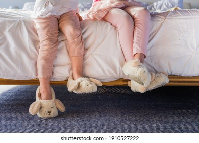 Girls' legs on white bed wearing cute slippers.  Sisters in pink clothes.