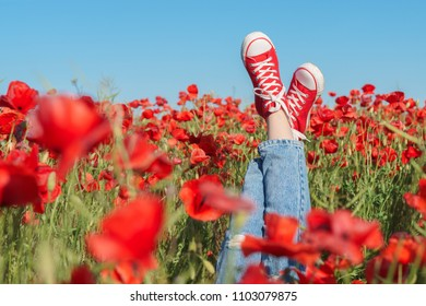 Girls legs in red sneakers in a poppy field. Joy and fun concept.