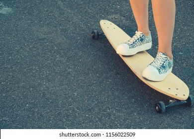 Girls legs standing on longboard closeup and a lot of copyspace