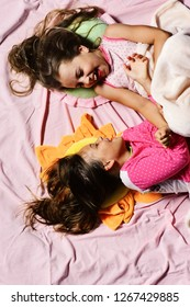Girls lie on white and pink bed sheets background tickling. Pajama party and childhood concept. Schoolgirls in pink pajamas wallow on colorful pillows, top view. Kids with happy faces have rest in bed
