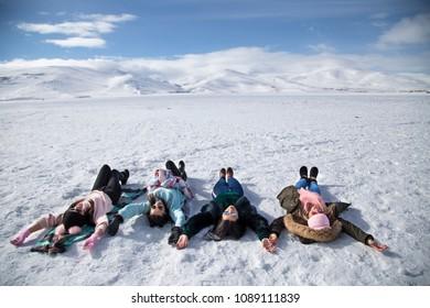 Girls lieing on the frozen Cildir Lake (Cildir Golu), Ardahan nearby Kars - Turkey 2018