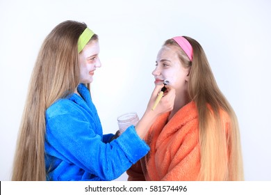 Girls with long hair in bathrobes spa treatments. Applying cream on face. Skin care in studio on white background