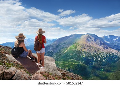 Girls looking at beautiful summer mountains landscape, on hiking trip, on  top of  mountain rock. View from Trail Ridge Road.Rocky Mountains National Park, Colorado ,USA.
