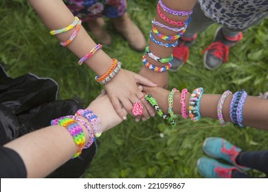 Girls with loom bracelets putting their hands together