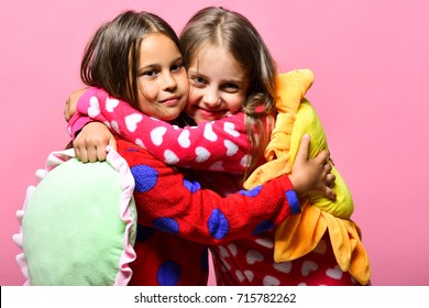 Girls with loose hair hug each other. Kids with smiling faces hold green and yellow sun pillows. Friends in pink polka dotted pajamas isolated on pink background. Pajama party and childhood concept
