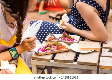 Girls at lunch on a summer terrace cafe, summer festival on the street. Сhat and street food