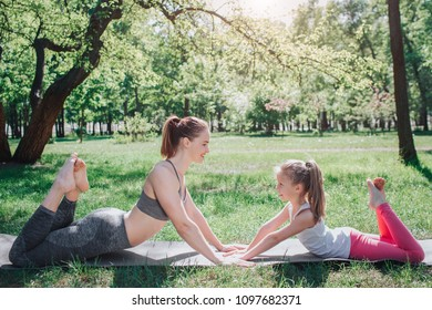 Girls are lying face to face and touching each other's hands. They are keeping their upper-body up when they are lying on the carimate with their low part of body. They are keeeping their toes up