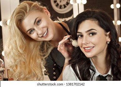 Girls make makeup in beauty salon. Blonde and brunette with backlit mirror background. Delicate and fun customer service.