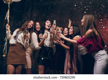 Girls make a New Year wish and drinking champagne. Happy group of attractive girls dancing with glasses of champagne