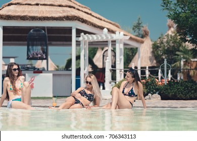 Girls meeting up for drinks, having fun on tropical island resort, best holiday ever, drinking cocktails near the beach bar, wearing sunglasses feeling happy on beautiful summer terrace green resort
