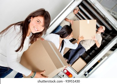 Girls moving house and unloading boxes from a truck