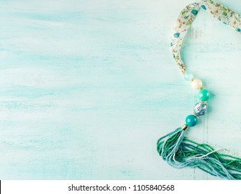 Girl's necklace on turquoise background. Blog banner