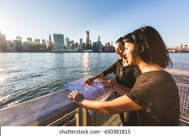 Girls in New York looking at city map . Happy young women enjoying the trip to New York and checking the map. Manhattan skyscrapers on background. Travel and lifestyle concepts