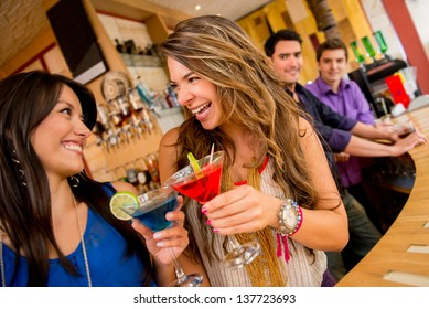 Girls night out having drinks and two men checking them out