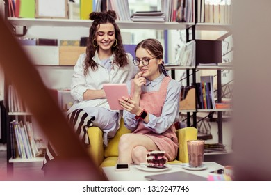 Girls observing content. Beaming cheerful ladies attentively looking on tablet while spending time in bookshop