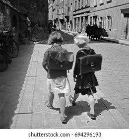 Girls with old fashioned backpacks walking in town