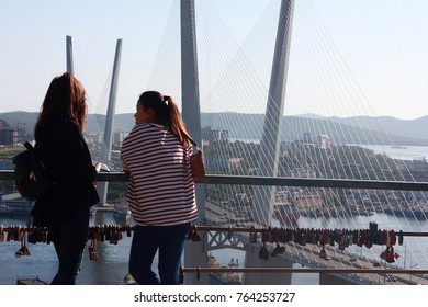 girls on the background of cable-stayed bridge across the Zolotoy Rog Bay in Vladivostok. Russia, Vladivostok. 23 September 2017