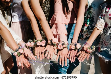 girls on beach show hands whis decorating boutonniere of flowers and ribbons. Buttonhole. Party Style boho. Maiden evening Hen-parties. Bachelorette. Close up. appearance above top view