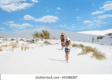 Girls on hiking trip  on the mountain desert, Blue sky with clouds in the background. Plants and shrubs growing on sand dunes.  White Sands National Monument, New Mexico, USA