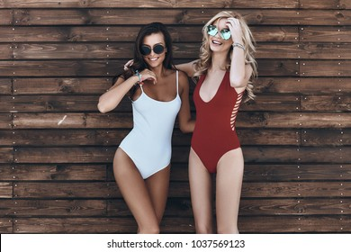 Girls only! Full length of two attractive young women in swimwear smiling while standing against the wooden wall outdoors