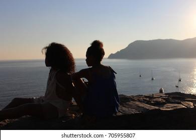 Girls overlooking sea at sunset