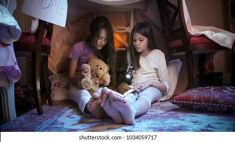 Girls in pajamas reading scary book with flashlight at night