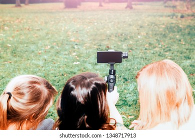 girls at the park using a phone for leisure activities