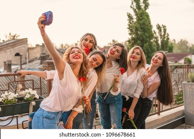 Girls Party. Beautiful Women Friends on the balcony or roof taking selfie with flowers At Bachelorette Party. They wear same clothes