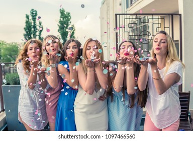 Girls Party. Beautiful Women Friends on the balcony Having Fun At Bachelorette Party. They are blowing confetti from hands. Selective focus