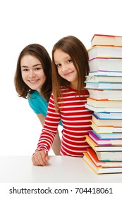 Girls peeking behind pile of books on white background