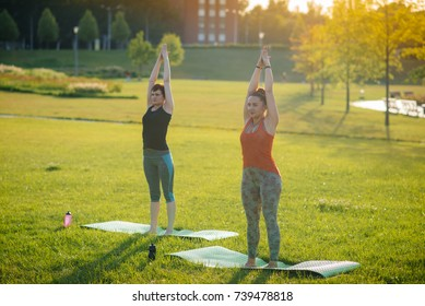 Girls perform yoga exercises in the evening in the park. Healthy lifestyle.